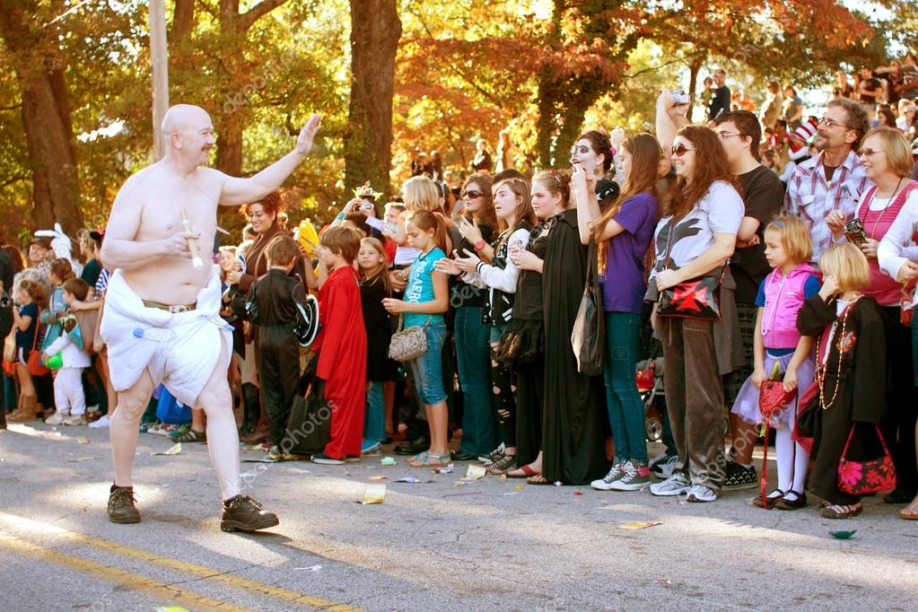 Atlanta, GA, USA - October 20, 2012:  An unidentified man dressed in a diaper as baby new year, walks in the Little Five Points Halloween parade, as spectators look on. The L5P Halloween parade is one of the largest in the southeast. — Stock Photo #17660941