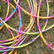 Colorful Hula Hoops Form Circles Lying On Grass - Stock Photo