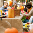 Постер, плакат: Parents And Kids Carve Pumpkins In A Public Park