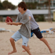 Teenage Boy Catches Football On Florida Beach - Stock Photo