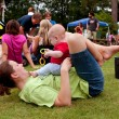Stock Photo: Mother Plays With Baby While Laying On Grass At Festival