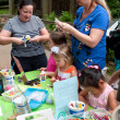 Stock Photo: Parents Help Kids With Arts And Crafts Project At Festival