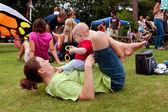 Mother Plays With Baby While Laying On Grass At Festival — Stock Photo