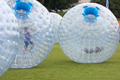 Kids Push Large Zorbs Around Grass Field At Summer Festival — Stock Photo