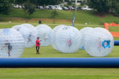 Several Kids Roll Around In Large Zorbs At Summer Festival — Stock Photo