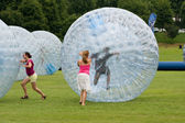 Women Push Large Zorbs Around Grass Field At Summer Festival — Stock Photo