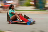 Motion Blur Of Girl Steering Car In Soap Box Derby — Stock Photo