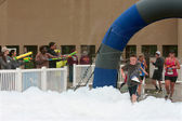 Runners Run Through Squirt Guns and Foam At 5K Race — Stock Photo