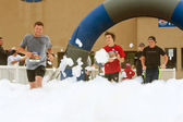 Male Runners Run Through Foam At Finish Line Of Race — Stock Photo