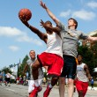 Stock Photo: MShoots Against Defender In Outdoor Street Basketball Tournament