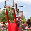 Stock Photo: Young MJumps High In Outdoor Basketball Slam Dunk Contest