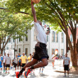 Stock Photo: Young MLeaps To Dunk Basketball During Outdoor Street Tournament