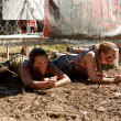 Young Women Crawl Under Electrified Fence In 5K Obstacle Race — Стоковая фотография