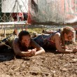 Stock Photo: Young Women Crawl Under Electrified Fence In 5K Obstacle Race