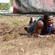 图库照片: MCrawls Under Electrified Fence At 5K Obstacle Course Race