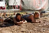 若い女性 5 k 障害物競走で電化フェンスの下にクロールします。 — ストック写真