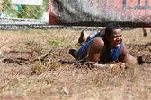 5 k の障害物コースのレースで電気柵の下で男をクロールします。 — ストック写真
