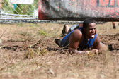 Man crawlt onder geëlektrificeerde hek bij 5 k hindernissenparcours race — Stockfoto