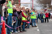 Spectators Cheer Oncoming Participants In Small Town Race — ストック写真