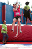Young Woman Swings With Rope In Crazy Obstacle Race — Stock Photo