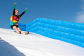 Woman Wearing Superhero Costume Goes Down Obstacle Race Slide — Stock Photo