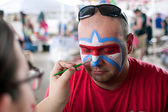 Man Gets Lafleur Symbol Painted On Face At Festival — Stock Photo