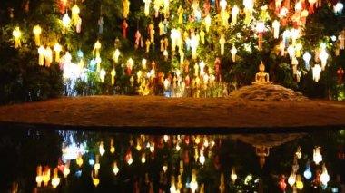 Guld buddha bild under vackra lantern träd och avspegling av damm — Stockvideo