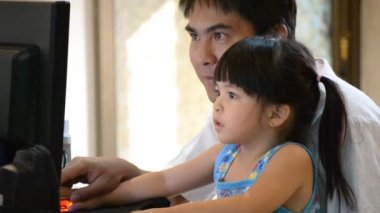 Asian father teach cute daughter playing computer — Stock Video