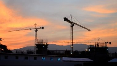 Time lapse silhouette crane working in construction site on dusk time — Stock Video
