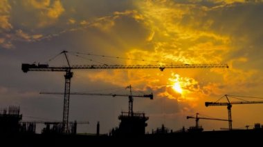 Time lapse sunset and silhouette crane working in big construction site — Vídeo stock