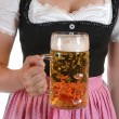 Young woman with a beer mug, dressed in a Bavarian dirndl — Stock Photo #12064413
