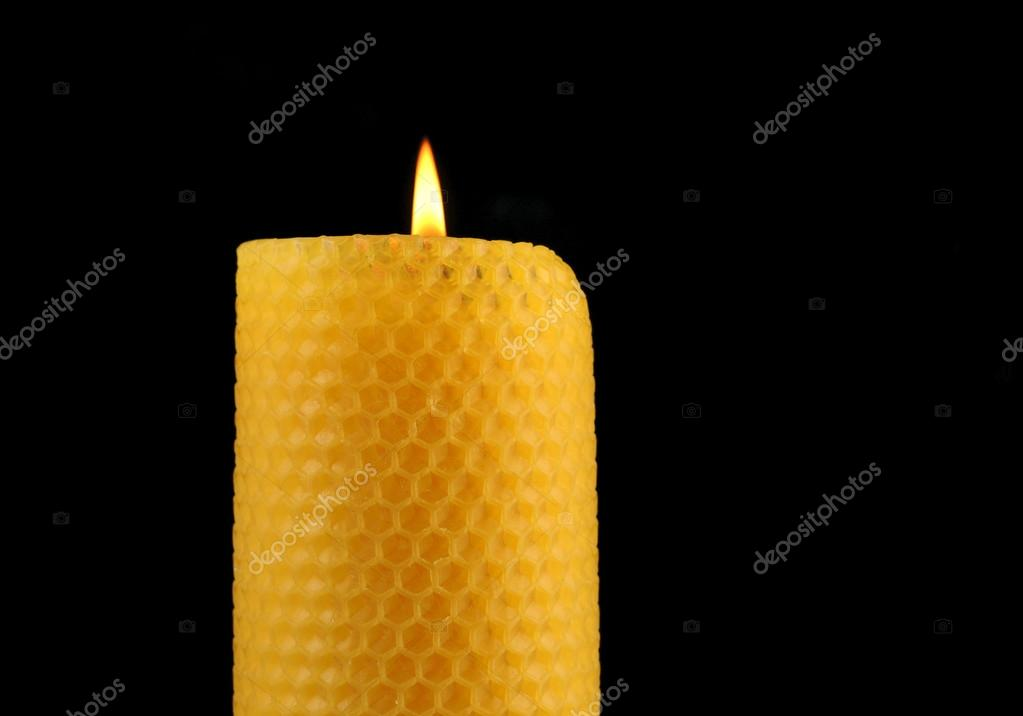Beeswax candle in front of a black background — Photo #12064441