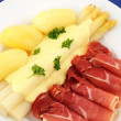Main course of white asparagus, sauce hollandaise, potatoes and Serrano ham — Stock Photo