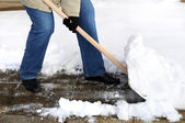 Woman is shovelling snow — Stock Photo