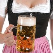 Young woman with a beer mug, dressed in a Bavarian dirndl — Stock Photo