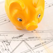 Construction plan with piggy bank as symbol for building a house - Stock Photo