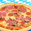 Fresh pizza with salami and white mushrooms on a table, decorated in the colors of Bavaria white and blue — Stock Photo #12469275