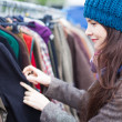 Woman choosing clothes at flea market. — Stock Photo