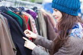 Woman choosing clothes at flea market. — Foto de Stock