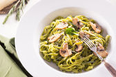 Tagliatelle pasta with pesto on white plate — Stock Photo