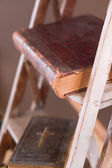 Old books on aged white ladder — Stock Photo