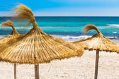 Beach, blue sea and straw umbrellas on Mallorca island, Spain — Stock Photo