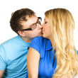 Stock Photo: Young min glasses and blond girl in blue shirt kissing isolat