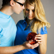 Young man in glasses and beauty blond girl holding red ball for — Stock Photo #13270977