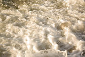 Waves rolling in towards the shore resulting in foamy water — Stock Photo