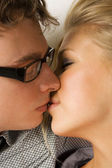 Young man in glasses and beauty blond girl kissing, side view — Stock Photo
