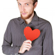 Young man with beard in grey shirt holding red paper heart on hi - Stock Photo