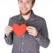Young man with beard in grey shirt holding red paper heart and s — Stock Photo