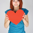Young redhead girl smiling and holding red paper heart, looking — Stock Photo