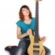 Young beauty redhead girl sitting and holding bass guitar, looki — Stock Photo